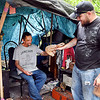 John P. Cleary | The Herald Bulletin<br /> Roger McDonald takes a package of food and water from Brandyn Barnes  as Barnes and others from Man4Man Ministries pooled their money and bought food and water to pass out to people living in the homeless camp near White River Monday.