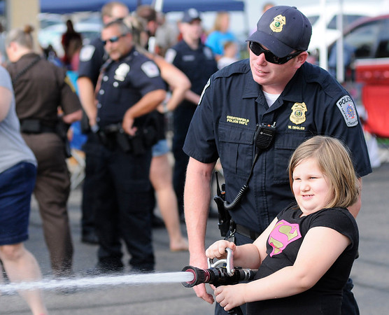 Don Knight   The Herald Bulletin<br /> Ellie Glant, 7, aims a fire hose as Chesterfield Police Chief William Ingles looks on during National Night Out on Tuesday.