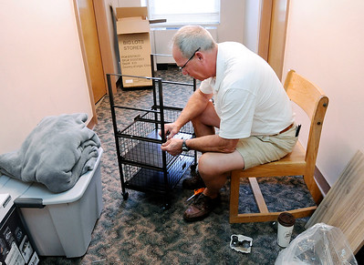 Don Knight   The Herald Bulletin Pete Monagham from Dublin Ohio assembles a cart for his son Gavin's dorm room in Dunn Hall on move-in day at Anderson University on Thursday.