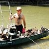 Don Knight | The Herald Bulletin<br /> Michael Moore arrives at the boat ramp with a full canoe including an abandoned lawn mower and scooter during the White River Watcher's annual cleanup on Saturday. About 70 people turned out for the event which takes place later in the year now to take advantage of the lower water levels that are typical in late Summer. If you'd like to learn more about the group they meet on the third Monday of each month at the library.