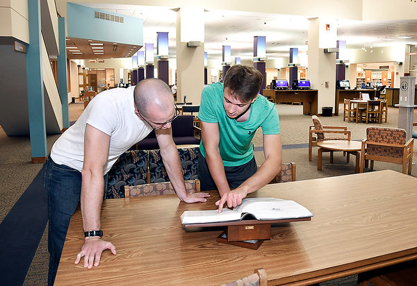 John P. Cleary | The Herald Bulletin<br /> Joshua Kerry and Adam Retych look up a word in the dictionary during their visit to the Anderson Public Library Friday afternoon. The library is  planning a $2.5 million remodeling of the ground floor of the facility.
