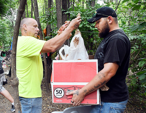 John P. Cleary | The Herald Bulletin<br /> David Ball grabs sacks of food as Brandyn Barnes holds the box as they and others from Man4Man Ministries bought food and water to pass out to people living in the homeless camp near White River Monday.
