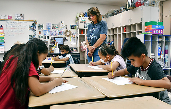 Donna Allen looks over her third grade students at Anderson Elementary School Friday as they worked on a math sheet.