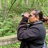 Anita Vega uses a pair of binoculars to observe a distant cardinal during a bird walk Saturday morning at Mounds State Park.