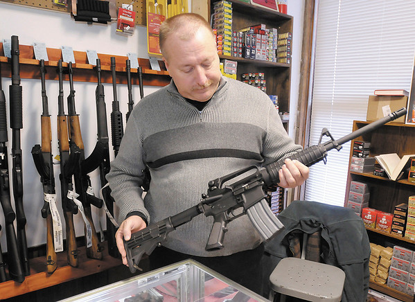 Mark Cole holds a Bushmaster AR-15 at his Buck Shot Guns and Ammo shop in Anderson.