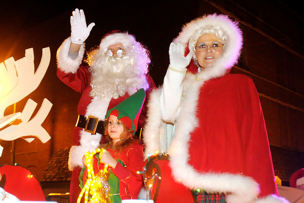 Santa, Mrs. Claus and an elf ride on a float in the Alexandria Christmas parade on Friday.