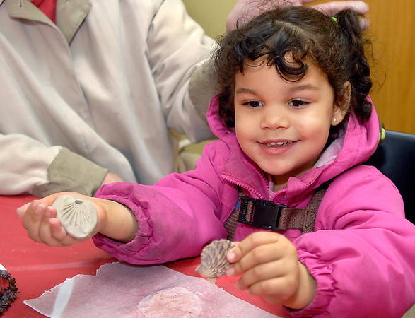 Malaya Legg, 3, shows off her shell clay ornament she made during Winterfest activities at the Anderson Center for the Arts Friday.