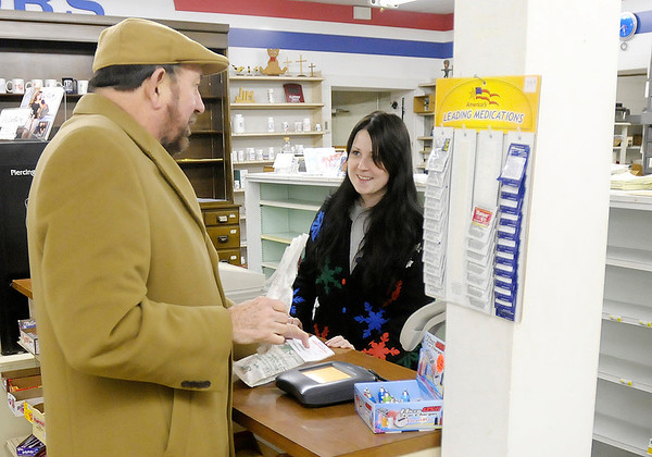 Ashley Emmons checks out long time customer Mike Cornell as Gwinn's drug store closed for the last time on Wednesday.