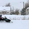 A snowmobile drives through Meadowbrook park on Wednesday. As the snow storm diminished people started digging out and have fun in the snow.