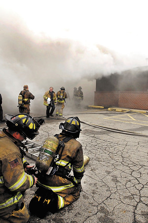Anderson firefighters battled a smoky fire at 2209 E. 10th Street that housed B & D Needful Things Monday morning.  Here firemen were coming out to get fresh air bottles to continue battling the blaze.