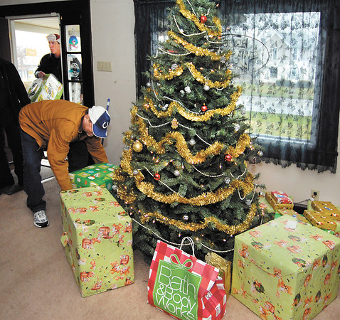 Randy Hollon, of Veterans of Madison County, sets down gifts next to the tree as Troy Castner, of the UPS Store, brings more gifts through the door of Ray Bigam's home where the two groups helped make the disabled Navy veteran's Christmas brighter.