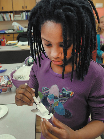 Maple Ridge Elementary School fourth grader Symone Kinnebrew works on making her snowman Christmas ornament in Kim Warner's class Friday.  Symone is part of Maple Ridges' high ability program for gifted and talented students.
