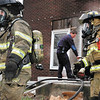 Anderson firefighters come out of a house fire Monday to get fresh airtanks as others were ventilating the structure in the 2000 block of Fletcher Street Monday.