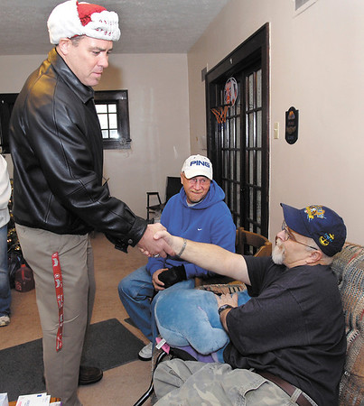 Troy Castner, owner of the UPS Store, greets disabled Navy veteran Ray Bigam as Rick Shaw, center, president of Veterans of Madison County, looks on.  The VMC along with the UPS Store came together to brighten Bigam's holiday.<br /> <br /> <br /> <br /> <br /> Veterans of Madison County and the UPS Store help Ray Bigam, a disabled Navy veteran, with Christmas.