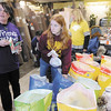 Alysia Eversole, left, and Kelsey Thurber select food and treats for a pet owner during a Ernie's Heart Pet Food Pantry distribution at the Showcase of Carpets on Saturday. Ernie's Heart is without a space of its own right now so Eversole, who owns the Showcase of Carpets, is hosting the distributions.