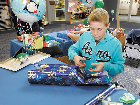Derrick Cook, 16, wraps presents at the Mounds Mall as a fundraiser for the YMCA Judo Club on Saturday. Derrick isn't a member of the club but his brother Quentin is. This is the fourth year for the fundraiser which help send club members to national and international competitions.