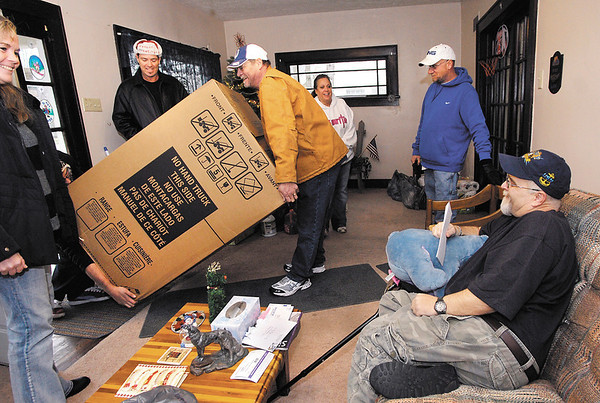 Ray Bigam, front right, a disabled Navy veteran, smiles as members of Veterans of Madison County and the UPS Store bring in a new stove for Bigam's kitchen.  The two groups came together to help make the Navy veteran's Christmas brighter.