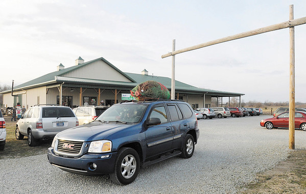 With their tree tied to the roof of their SUV, a family leaves Piney Acres in Fortville on Saturday December 1, 2012.