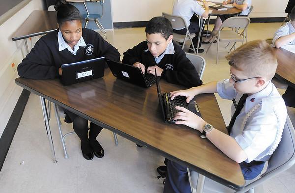 From left, Jasmine Ingram, Dakota Sims and Callaway Aranda work on netbook computers at the Anderson Preparatory  Academy.