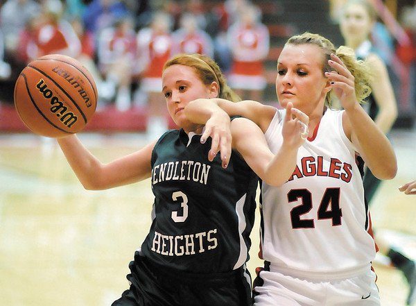 Pendleton Heights' Meghan Dawson and Frankton's Natalie McGuire reach for a loose ball during the first round of the Madison County Basketball Tournament on Saturday.