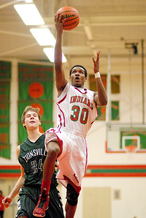 Armon Daniels drives past Zionsville player Derrik Smits to put two points on the board for the Indians.