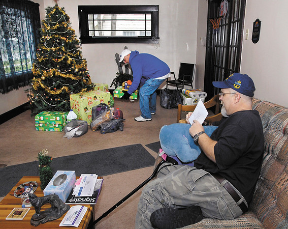 Rick Shaw, president of Veterans of Madison County, sets down gifts next to the tree as disabled Navy veteran Ray Bigam watches.  The VMC along with the UPS Store came together to brighten Bigam's holiday.