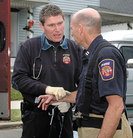 Anderson Fire Department Capt. Brad Corbin takes vital signs on Capt. Gary Cochran after he had been fighting a house fire in the 2000 block of Fletcher Street Monday.