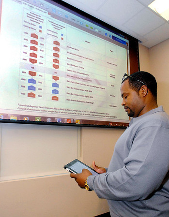 Lindsay Brown, CEO of the Urban League of Madison County, works his tablet to call up the document that appears on the large screen as part of the State of the Black Youth Report held by the Anderson chapter of Indiana Black Expo Tuesday.