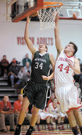 Pendleton Heights' Kurt Talbert drives for a layup as he is guarded by Frankton's Jordan Reeves. Reeves was called for goaltending on the play.