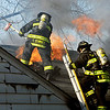 Firefighters work to open up the roof to help ventilate the structure as flames leap out as they battle a house fire at 13908 W. Daleville Road in Daleville Friday afternoon.