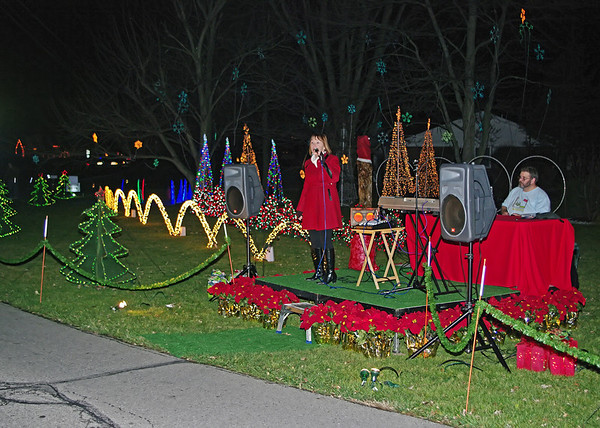 Grammy nominated singer-songwriter Judy Pancoast in concert at the Edge-Wood-Lights house at 2221 Winding Way in Anderson.  In the background operating the lights is homeowner Paul Wood.