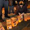 Dee Vester from Daleville lights luminaries at Anderson Animal Protection League on Friday. The luminaries are lit on the winter solstice, the longest night of the year, as a memorial to pets.