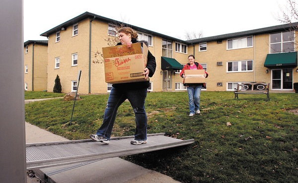 Autumn Elsworth, left, loads up another box as friend Farah Gard follows as Elsworth moves out of her Arbor Village apartment Thursday afternoon after the city condemned the complex Wednesday.  Elsworth has lived in the apartments for almost two years with her two children, ages 11 and 4, but now will move in with her parents to get through the holidays.