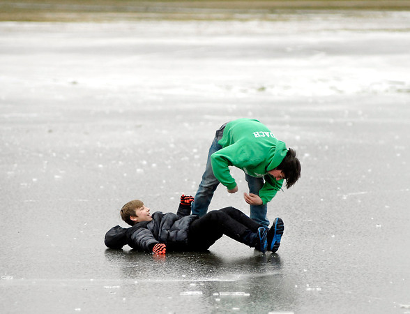 THB photo/John P. Cleary<br /> With the recent heavy rains and then bitter temperatures ponds of standing water turned to ice like this large area in the middle of Athletic Park in Anderson.  But James Pierce, 12, and his cousin Gerald Watkins, 17, along with other family members, found the frozen surface a great place on a Christmas afternoon to get outside and slide and play around on.