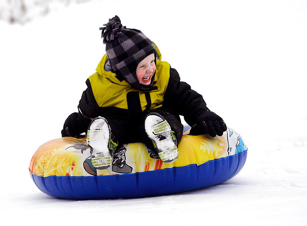 THB photo/John P. Cleary<br /> Ezra Skaggs, 4, giggles as he slides down the hill at Shadyside Park on his inflatable tube where he and his grandpa, Mike Kelly, were enjoying the fresh snow Monday afternoon.