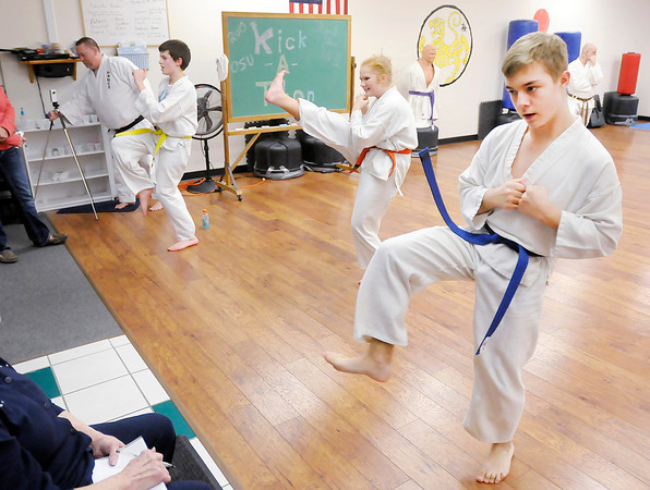 Don Knight / The Herald Bulletin<br /> From right, Trey Neal, Hailey Greer and Carson Tipton take part in a Kick-O-Thon at the Training Academy of Shotokan Karate in the Mounds Mall on Friday. Students gathered pledges and then performed as many kicks as they could in an hour with proceeds going to help families in need this Christmas.