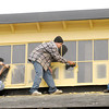 Don Knight / The Herald Bulletin<br /> From left Evan Beckham, Lanny Westrater and General Contractor Larry Westrater scrape excess paint from newly painted windows at Barber Manufacturing in Anderson on Wednesday.