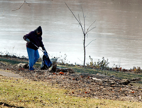 """THB photo/John P. Cleary<br /> A lady who calls herself a 'local environmentalist' picked up trash out of the debris that had been washed up from Shadyside Lake due to the recent flood waters Thursday. The lady, who did not want to give her name said, """" If everybody would carry a trash bag and pick up after themselves, we would not  have this problem in our parks."""""""
