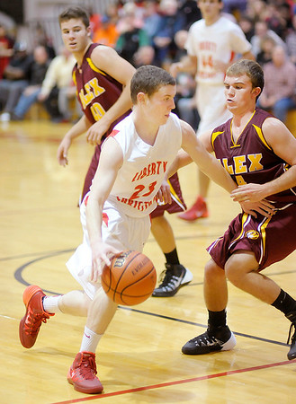 Don Knight / The Herald Bulletin<br /> Liberty Christian's Ben Bowen drives to the basket as he is guarded by Alexandria's Layton Carroll as the Lions hosted the Tigers on Saturday.