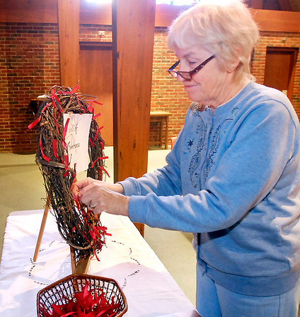 THB photo/John P. Cleary<br /> Emily Carter ties ribbons with names of friends lost to AIDS onto a Wreath of Remembrance at the World AIDS Day Prayer Service at St. Mary's Catholic Church Monday.