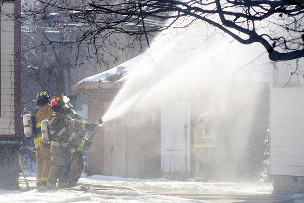 Don Knight / The Herald Bulletin<br /> AFD fire fighters protect a neighboring house during a house fire on 11th Street on Thursday.