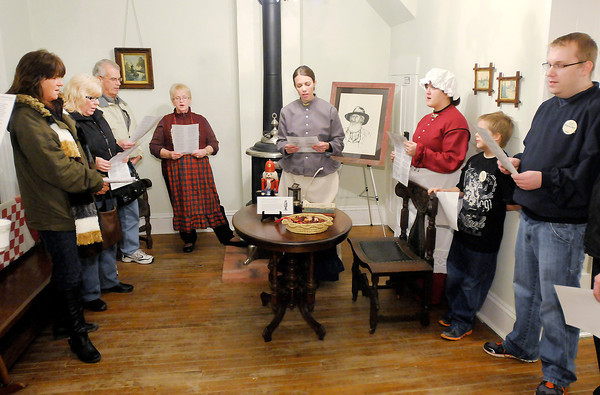 Don Knight / The Herald Bulletin<br /> Mounds State Park naturalists, volunteers and guests sing Christmas Carols as the park hosted Christmas at the historic Bronnenberg home on Saturday. Staff hope to make the new event a Christmas tradition.