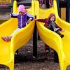 THB photo/John P. Cleary<br /> Modlene Campbell, 5, and Jensen Thompson, 4, race each other down the dual slides as they enjoy an outing with family members at Shadyside Park over the weekend taking advantage of the warmer weather.