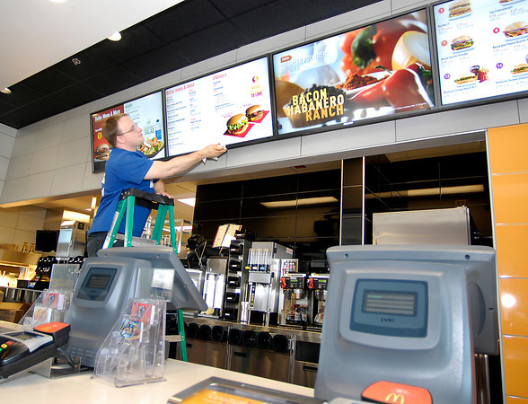 THB photo/John P. Cleary<br /> Tommy Brown, 1st assistant manager, cleans off the new menu board as the staff of the new McDonald's restaurant at 2830 Broadway in Anderson  prepares to reopen This coming Tuesday morning.  The restaurant was closed the first of October and the building torn down and this updated new facility built.