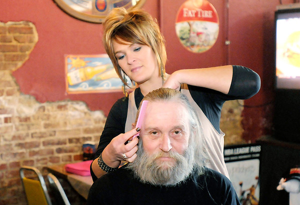 Don Knight / The Herald Bulletin<br /> Megan Dowden from Trends Hair Salon in Fishers cuts Vietnam Veteran Stan Rockhold's hair at Mardi Gras Pizza and Pub in Lapel on Saturday. Rockhold agreed to cut his hair and beard if $500 in donations could be raised for the Toys for Tots charity.