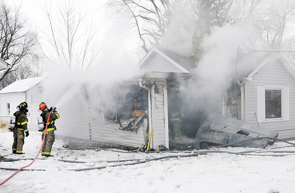 Don Knight / The Herald Bulletin<br /> Anderson fire fighters respond to a fire started in a garage in a home on Ridgewood Drive on Thursday.