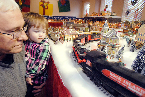 THB photo/John P. Cleary<br /> Tim Harmon, of Alexandria, holds his granddaughter Anistynn Warrum, 2, to get a closer look at the train as it goes by at Larry Davenport's Christmas Village train display at the Paramount Theatre.  Harmon was there with family to check out the annual Festival of Trees and all the different displays Tuesday afternoon.  The festival runs through December 7.