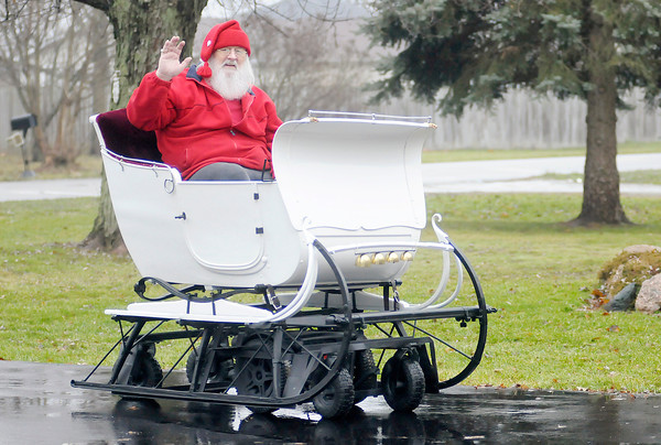 Don Knight / The Herald Bulletin<br /> Bill Wood adapted a mobility scooter to drive his antique sleigh.