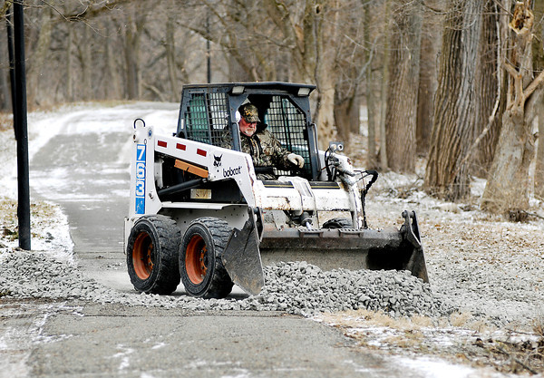 THB photo/John P. Cleary<br /> Mike Shocke, of the Anderson Parks Department, spreads out stone along the Shadyside Park trail on the west side of the lake Monday afternoon.  Workers were out backfilling areas along the trail system where recent flood waters had started to erode the banks around the lake.