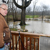 THB photo/John P. Cleary<br /> David Odom looks out from his parents porch in the 900 block of East 10th Street as the flood waters recede from around the house Monday. The property backs up to the newly constructed levee being installed to protect property owners but Odom claims that back flow preventers were not installed the same time piping was installed in the levee leaving the water to flow directly from the river through the pipes.